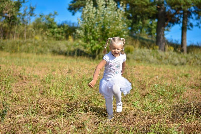 Skratta lilla flickan i den vita klänningen som stöter ihop med fältet i en solig eftermiddag arkivbild