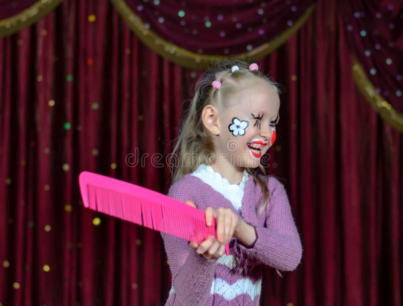 Skratta lilla flickan i komisk makeup royaltyfri bild