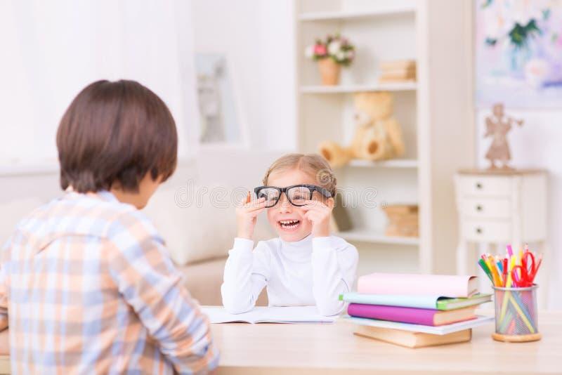 Skratta lilla flickan som försöker på hennes mammaexponeringsglas arkivbilder