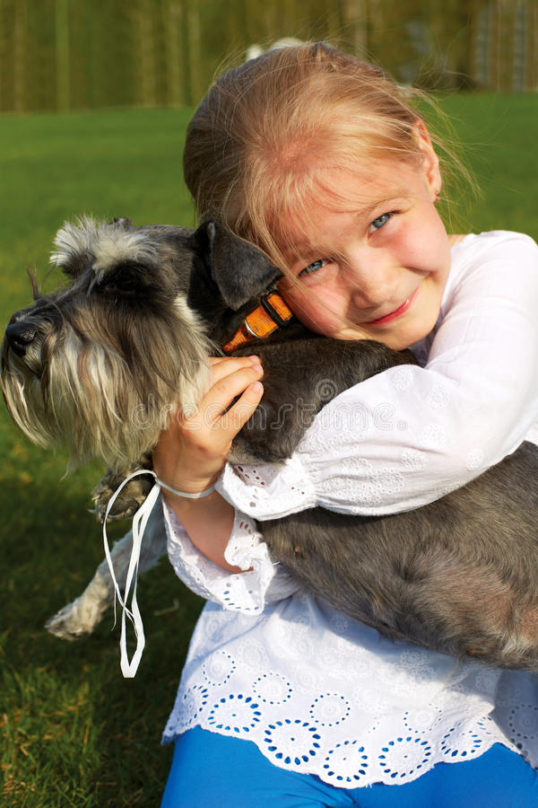 Skratta lilla flickan som kramar hennes hund royaltyfria foton