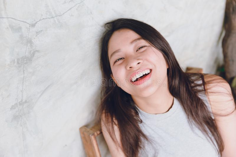 Skratta lyckliga roliga tider för den asiatiska thailändska kvinnaståenden arkivbild