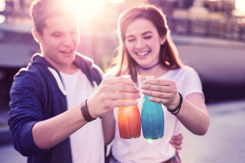 Skratta lyckliga unga par observera glasflaskor med förnyande drinkar arkivbilder