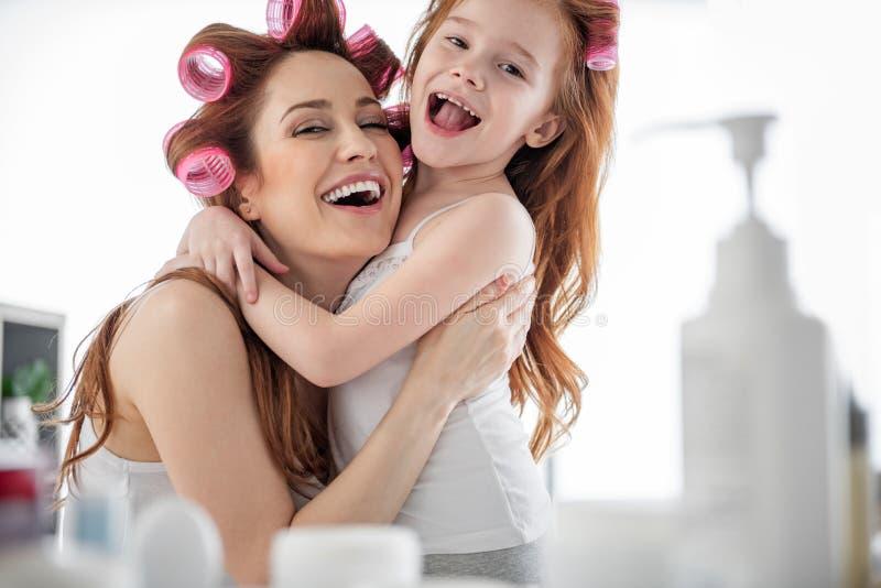 Skratta mamman och dottern i badrum hemma arkivfoto
