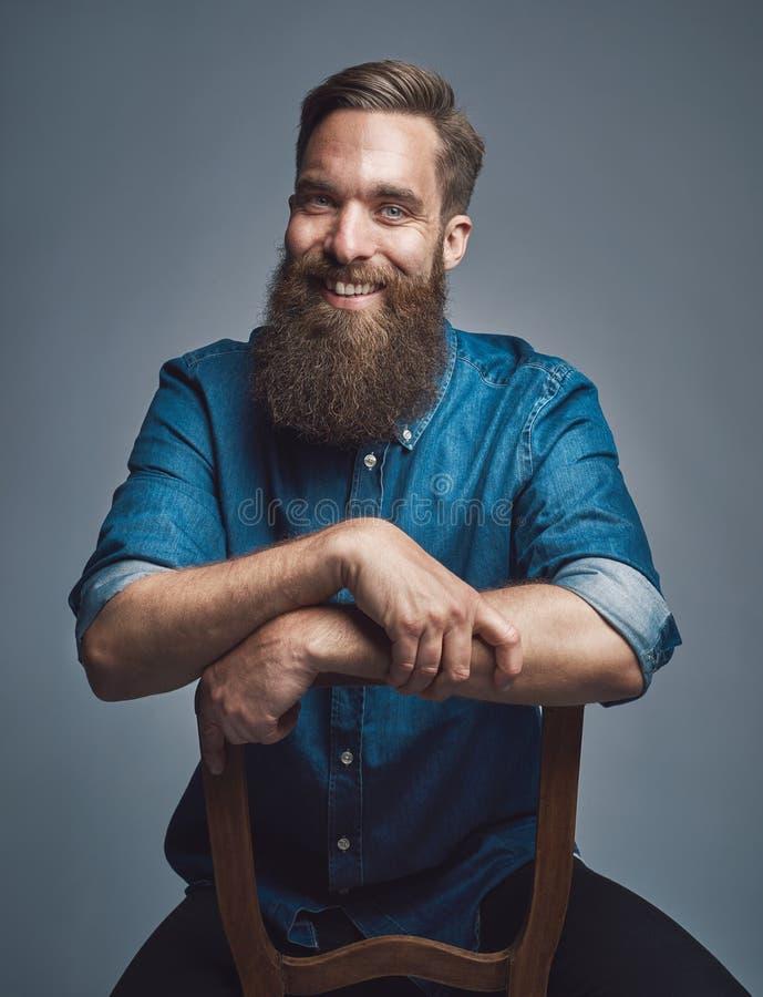 Skratta mannen med armar på baksida av stol över grå färger arkivbilder