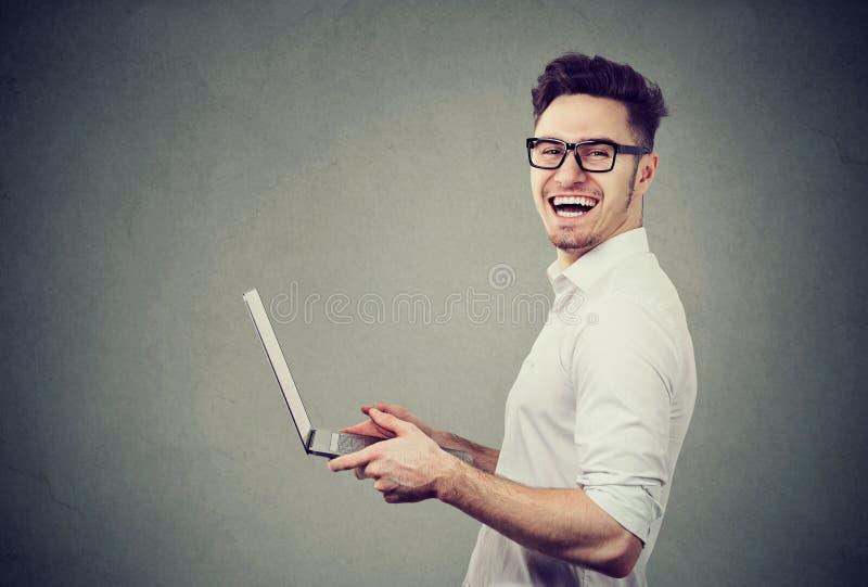 Skratta mannen med den moderna bärbara datorn arkivbilder