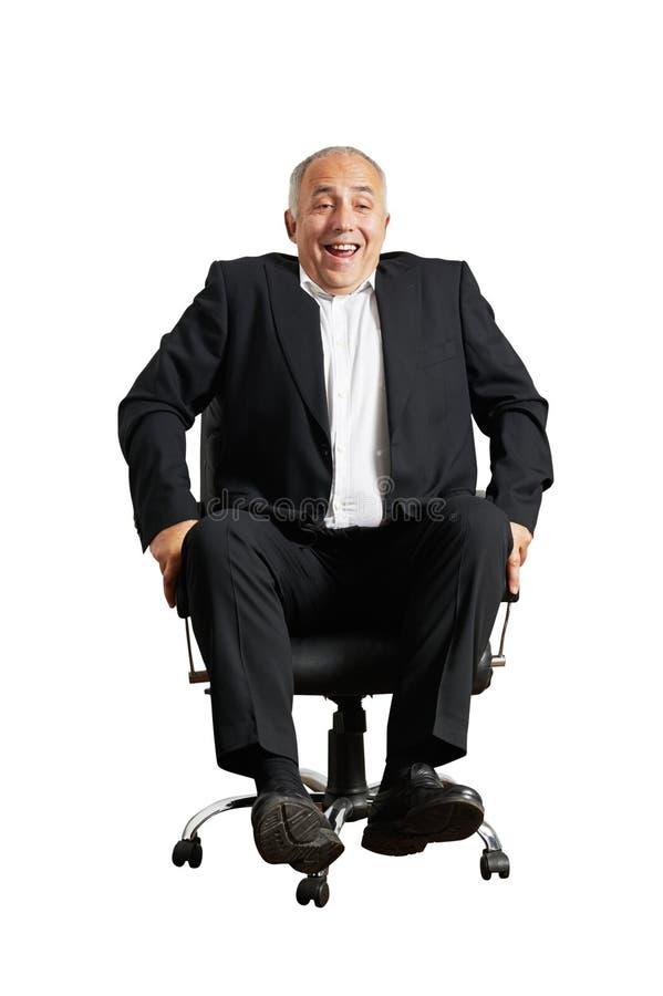 Skratta mansammanträde på kontorsstol arkivbilder