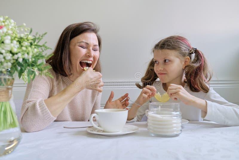 Skratta modern och dottern som dricker från koppar och att äta citronen arkivbild