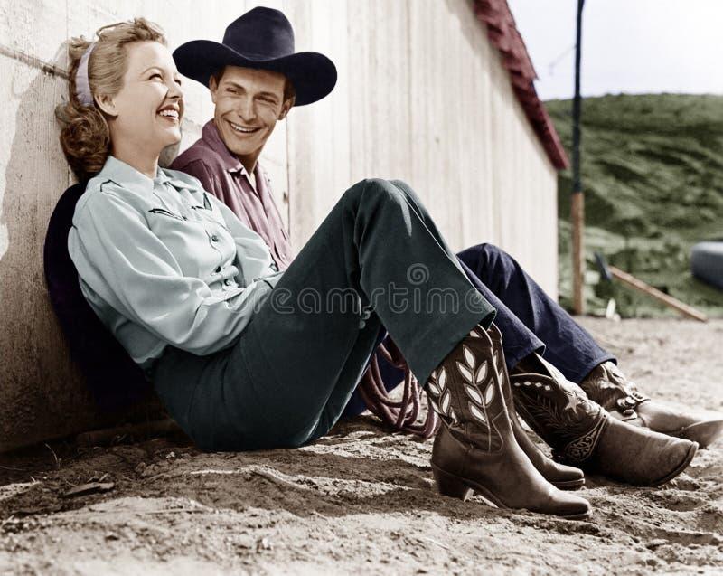 Skratta par i västra dresssammanträde på jordningen (alla visade personer inte är längre uppehälle, och inget gods finns Suppli royaltyfri foto