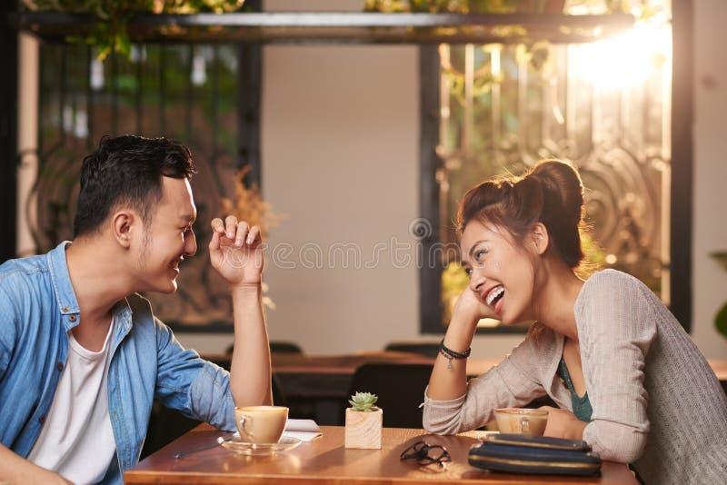 Skratta par på datum i kafé fotografering för bildbyråer