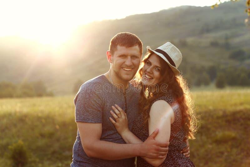 Skratta par som är förälskade på solnedgången i natur, bröllopsresa, berg, tillbaka ljus, mjukt ljus, sinnesrörelser som skrattar arkivbild