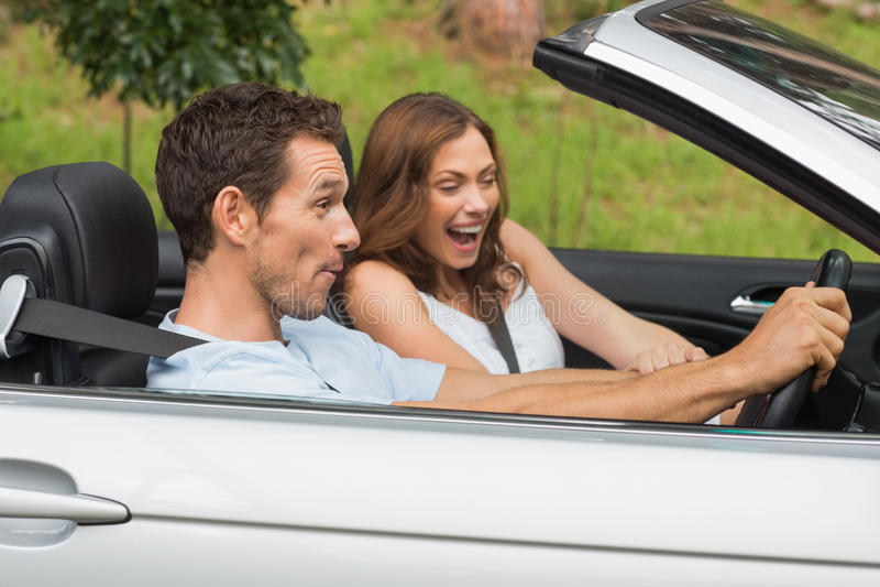 Skratta par som kör i en cabriolet arkivbild