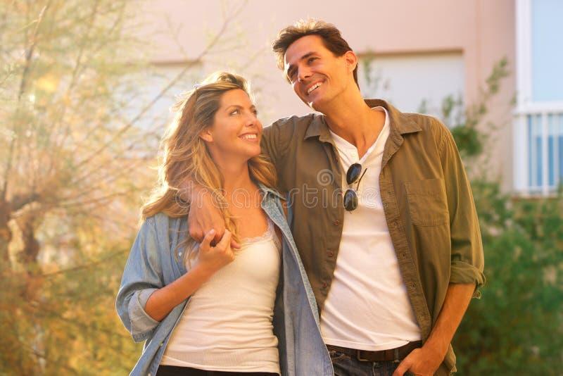 Skratta par som tillsammans går på datum i omfamning arkivbild