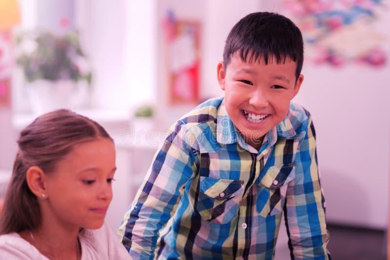Skratta pojkeanseende nära hans sittande klasskompis royaltyfri foto