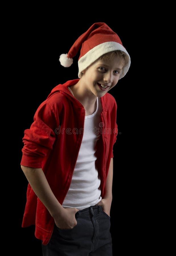 Skratta pojken i jultomtenhatten som isoleras på svart bakgrund arkivfoto