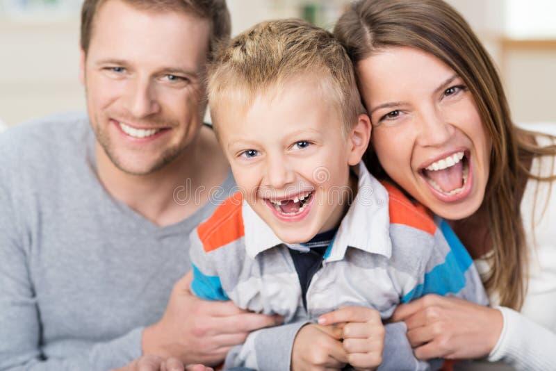 Skratta pysen med hans unga föräldrar royaltyfri foto