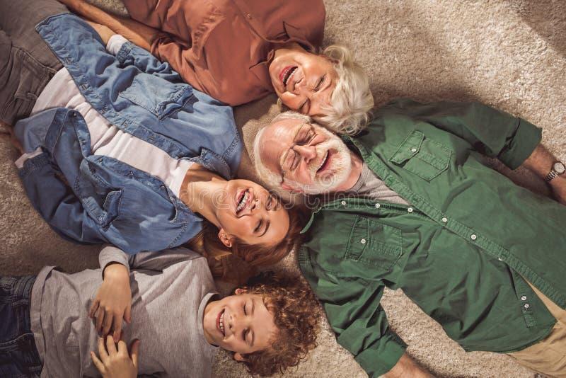 Skratta släktingar som lokaliserar på matta royaltyfri fotografi