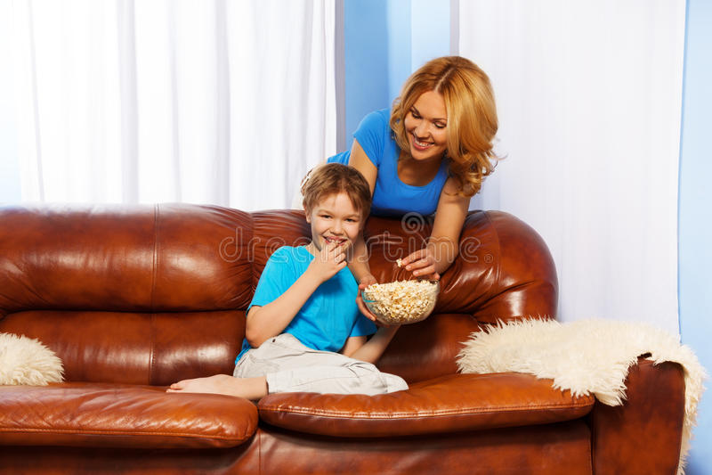 Skratta sonen som äter popcorn och den lyckliga modern arkivfoto