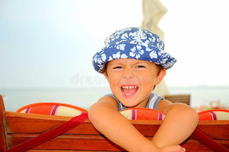 skratta stående för strandpojke arkivfoton