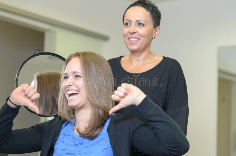 Skratta 20-talkvinnan på frisörer royaltyfri bild