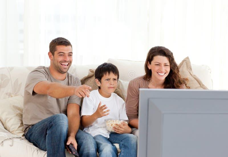skratta television för familj som håller ögonen på tillsammans royaltyfria foton