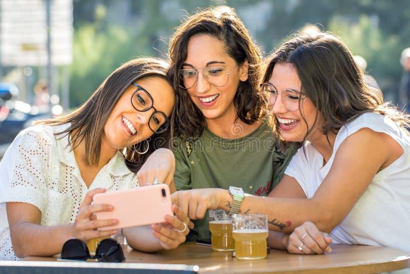 Skratta threesomeflickavänner med smartphonen på terrass royaltyfria bilder