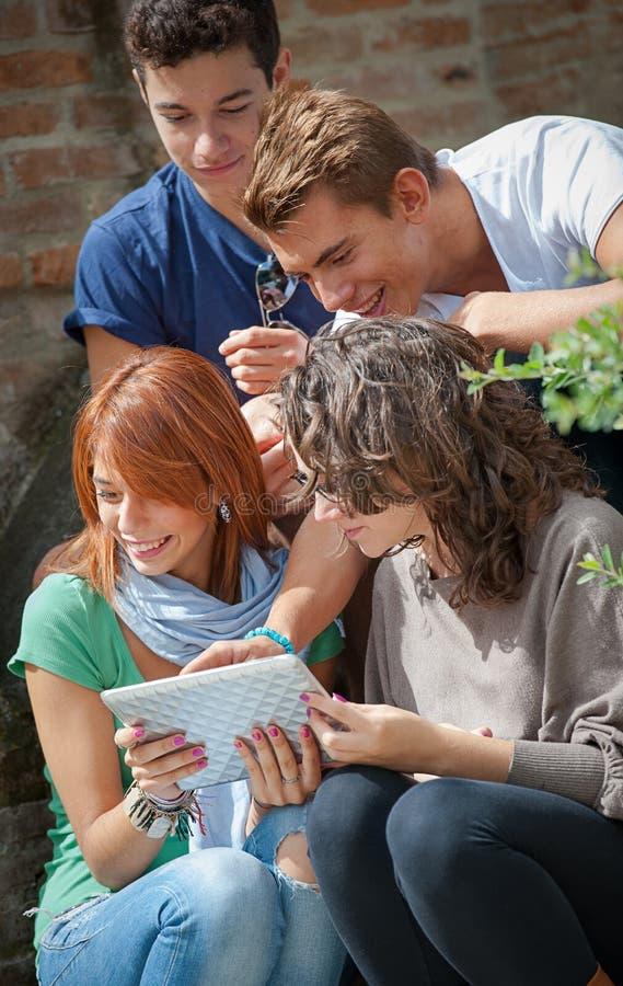 Skratta tonåringar som ser touchpaden royaltyfria bilder