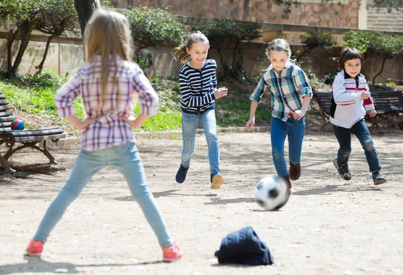 Skratta ungar som utomhus spelar gatafotboll arkivbild