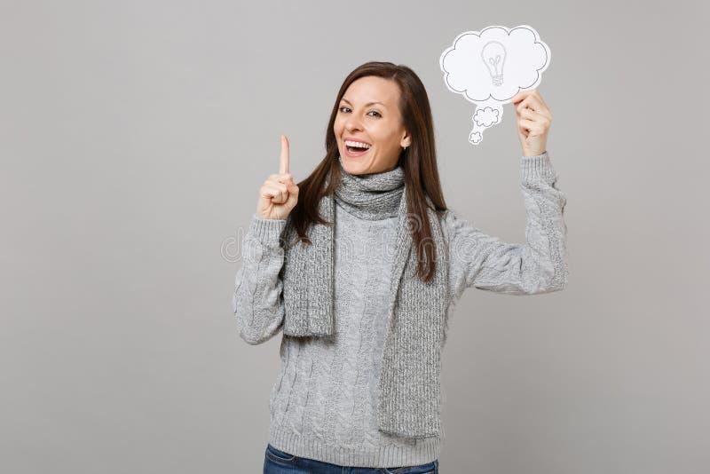 Skratta upp den unga kvinnan i tröja, säger halsdukinnehavpekfingret med stor ny idé, molnet med lightbulben som isoleras på royaltyfri foto