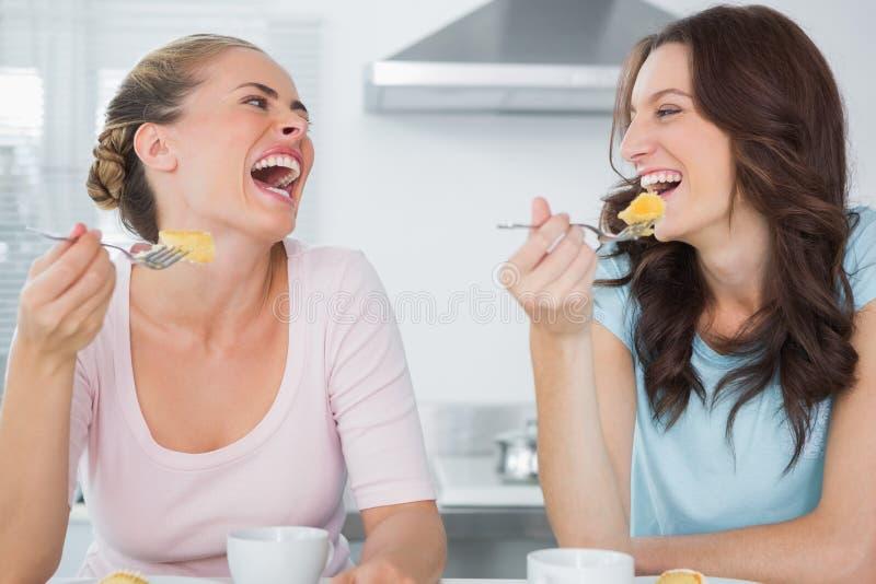 Skratta vänner som äter kakan och att ha kaffe royaltyfri bild
