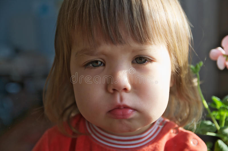 Skriande closeup för ledsen liten flickastående som inomhus, fördjupnings-, ensamhet-, spännings- eller trötthetsbegrepp ser kame royaltyfri bild