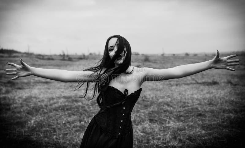 Skriande ledsen gothflicka i det höstliga fältet svart white arkivfoton