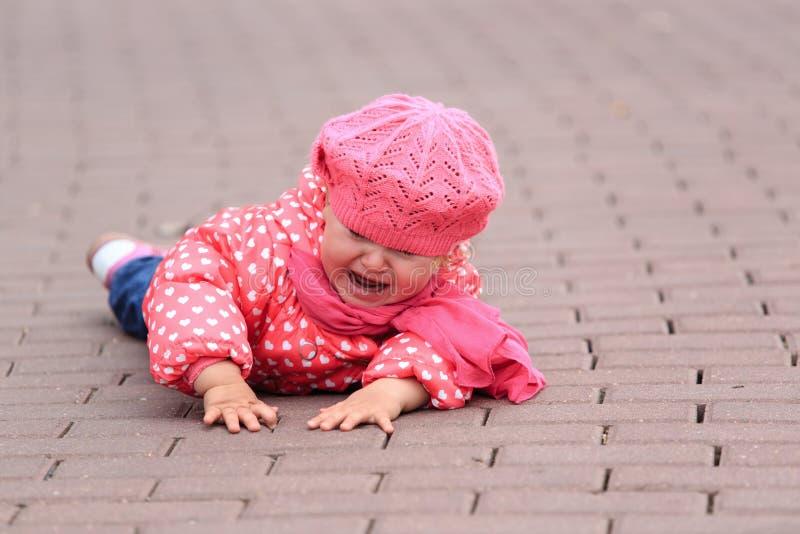 Skriande liten flickanedgång av på trottoaren royaltyfria bilder