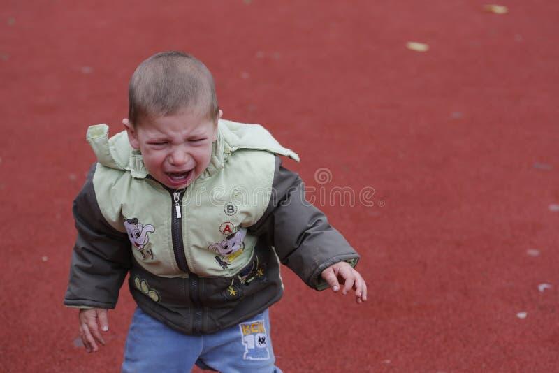 Skriande yttersida för litet barnbarn i lekplats royaltyfri bild