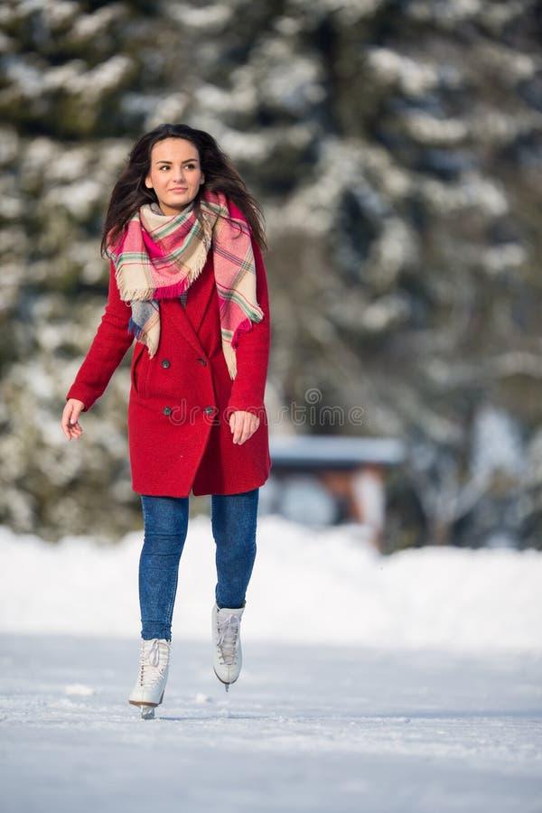Skridskoåkning för ung kvinna utomhus på ett damm royaltyfri bild
