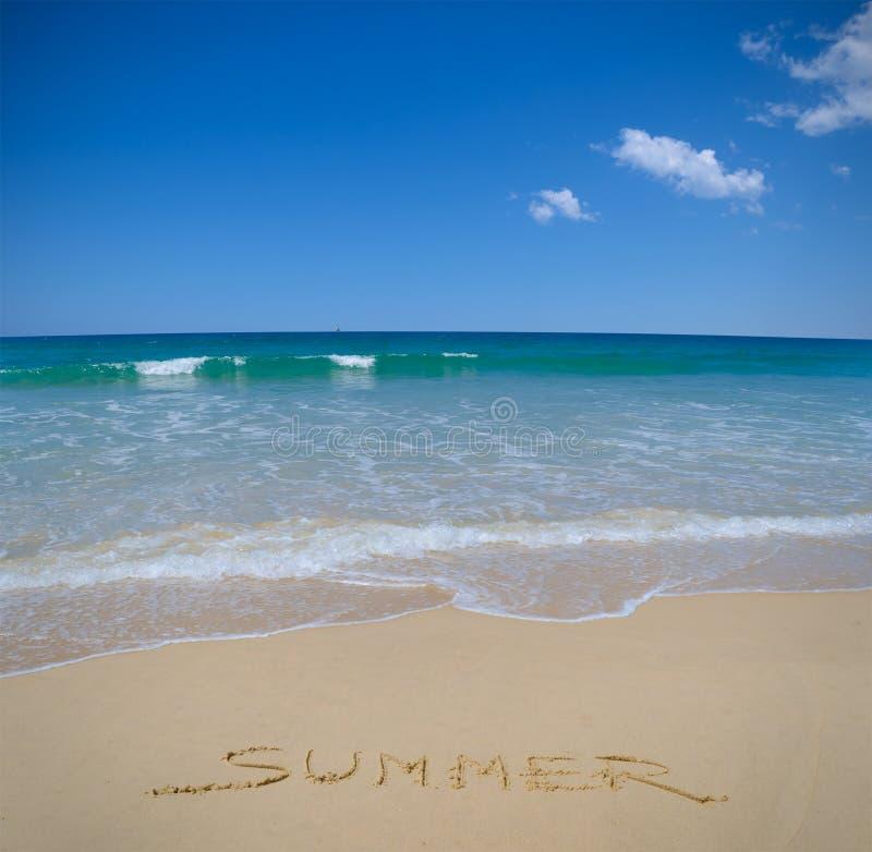 Skriftlig sommar i strandsand arkivfoto