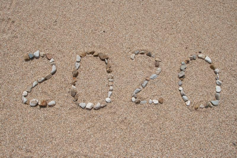 2020 skriftliga år på strandsanden arkivbild