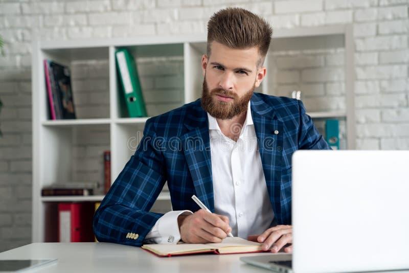 Skriftliga anteckningar för företagare som sitter vid skrivbordet Ung man gör affärsplaner med papper och datorer på sitt skrivbo royaltyfri bild