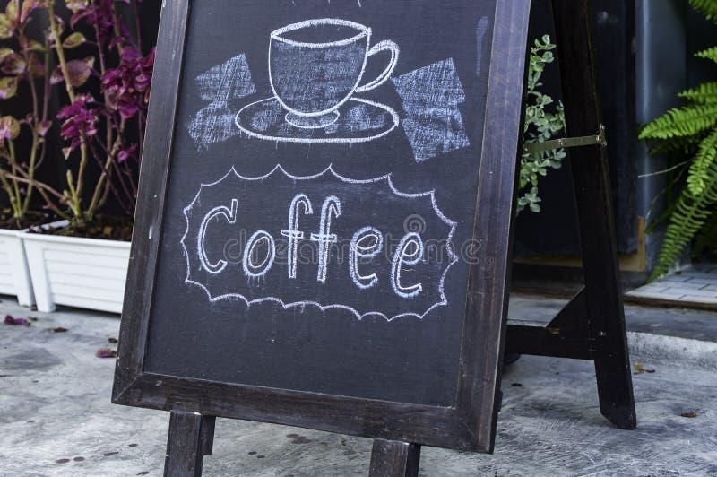 Skriftligt kaffemeddelande för hand mot svart tavlabegrepp arkivfoto