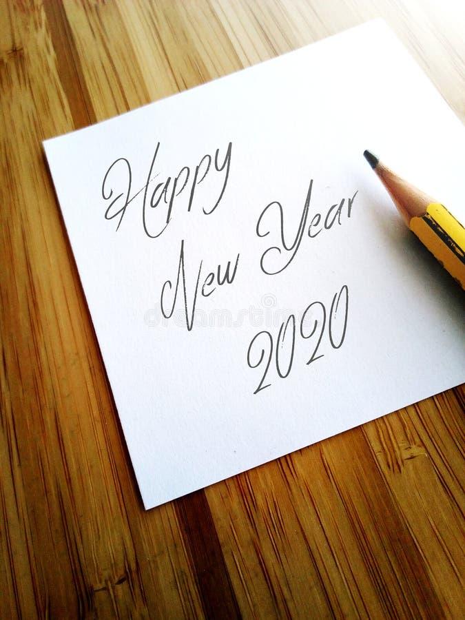 Skriftligt lyckligt nytt år 2020 med blyertspennan på pappersanmärkning royaltyfri bild