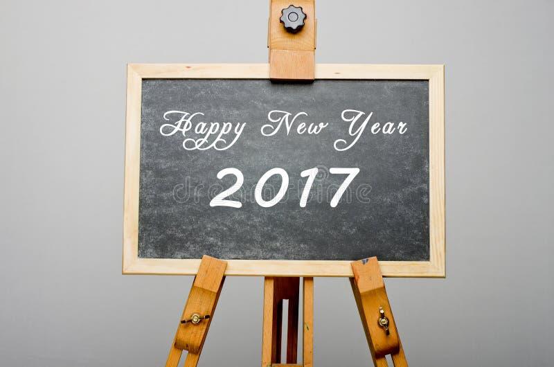 Skriftligt lyckligt nytt år 2017 på den svarta svart tavlan, stafflimålning fotografering för bildbyråer