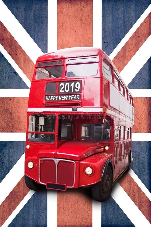 Skriftligt lyckligt nytt år 2019 på London en röd buss, Union Jack bakgrund royaltyfria foton