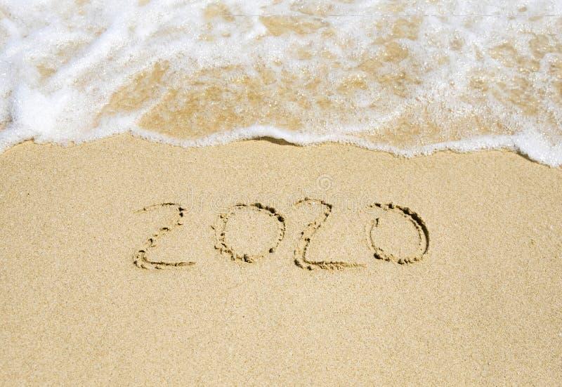 Skriftligt nytt år 2020 på strandsanden arkivfoto