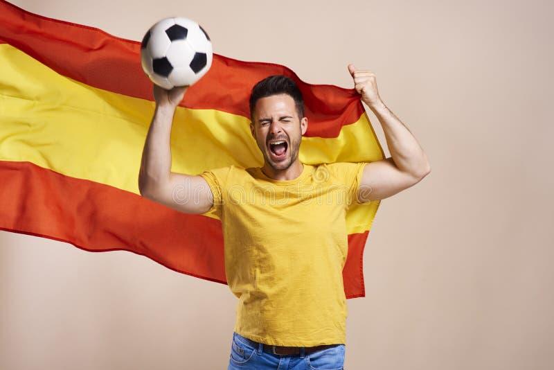 Skrika den spanska faninnehavflaggan och fotbollbollen arkivbild