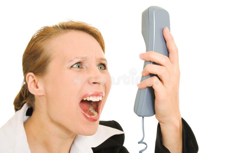 skrika för affärskvinnatelefon arkivbild