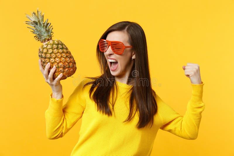 Skrika kvinnan i roliga exponeringsglas som griper hårt om näven som vinnaren som rymmer ny mogen ananasfrukt isolerad på den gul royaltyfria bilder