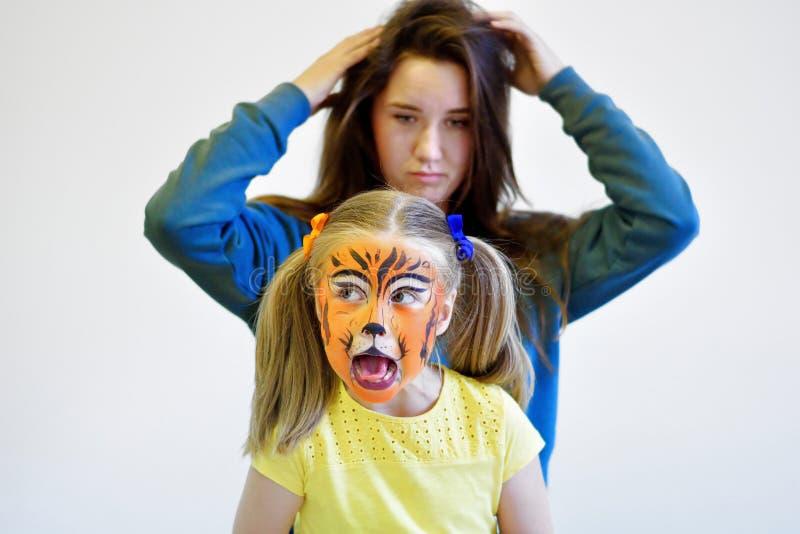 Skrikig flicka med den målade tigerframsidan och hennes moder arkivbild