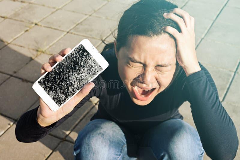 Skrikig kvinna som rymmer en skärmspricka smartphonen royaltyfri foto