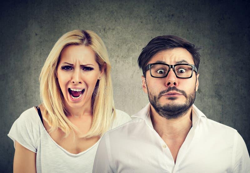 Skrikig och fruktansvärd man för ilsken tokig kvinna royaltyfri fotografi