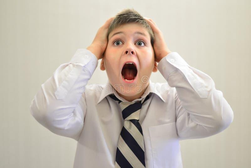 Skrikigt innehav för tonårig pojke hans händer bak huvudet royaltyfri foto