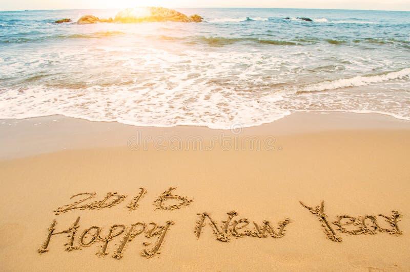 Skriv det lyckliga nya året 2016 på stranden arkivbild